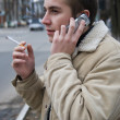 Young smoker on the phone — Stock Photo