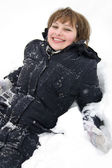Smiling girl laying in snow — Stock Photo