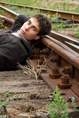 Young man laying on a railway tracks — Stock Photo