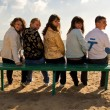 Group of smiling young on a bench — Stock Photo