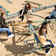 Pretty girls riding merry-go-round - Stock Photo
