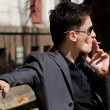 Smoking young man in sunglasses — Stock Photo