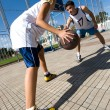 Stock Photo: Two young playing basketball