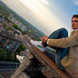 Young attractive man sitting on the roof — Stock Photo #3232052
