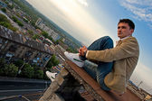 Young attractive man sitting on the roof — Stock Photo