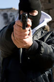 Armed criminal aiming you — Stock Photo