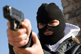 Criminal in mask aiming his target — Stock Photo