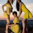 Royalty-Free Stock Photo: Three sexy young women in yellow dresses posing