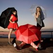 Three sexy chicks with umbrellas posing on the roof - Stock Photo