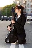 年轻漂亮的黑发姑娘接吻一把吉他 — 图库照片