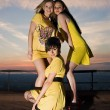 Three sexy young women in yellow dresses posing — Stock Photo