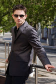 Young businessman in sunglasses leans on handrails — Stock Photo