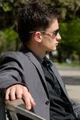 Man in zonnebril en jas zittend op een bankje in het midden van — Stockfoto