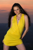 Sexy young brunette woman in short yellow dress — Stock Photo