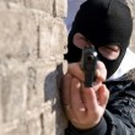 Постер, плакат: Criminal targeting into the camera with a gun