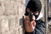 Criminal targeting into the camera with a gun — Stock Photo
