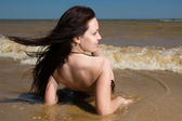 Young woman siitng under tidal waves — Stock Photo