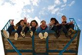 Empresa de cinco jóvenes sentados juntos — Foto de Stock