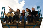 Company of five young sitting together — Stock Photo