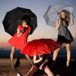 Three sexy chicks with umbrellas posing on the roof — Stock Photo