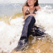 Young girl sits in water splashes at the beach — Stock Photo