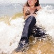 Young girl sits in water splashes at the beach — Stock Photo #3465221
