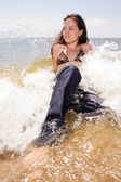 Young girl sits in water splashes at the beach — Foto Stock