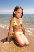 Küçük kız plajda otururken — Stok fotoğraf
