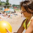 Little girl plays ball at crowded seaside — Stock Photo