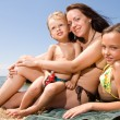 Royalty-Free Stock Photo: Young mom with kids at the beach resort