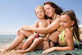 Young mom with kids at the beach resort — Stock Photo