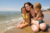 Young mom and her kids at the beach — Stock Photo