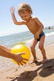 Little boy plas ball at the seaside — Stock Photo