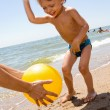 Little boy plas ball at the seaside — Stock Photo