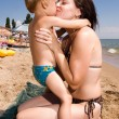 Stock Photo: Young mother kissing her son at beach