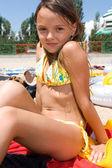 Little girl sunbathing at the beach — Stock Photo