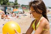 Niña juega a la pelota en la playa llena de gente — Foto de Stock