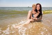 Ung mamma håller hennes son i händer på stranden — Stockfoto