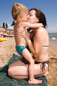 Young mother kissing her son at the beach — Stock Photo