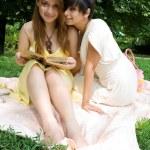 Yorgan yeşil çimenlerin üzerine oturmuş iki genç kız — Stok fotoğraf