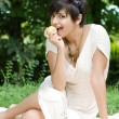 Stock Photo: Healthy young girl eating apple outdoors