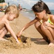 Two young kids digging sand at the beach - Stock Photo