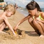 挖砂在海滩上的两个年轻孩子 — 图库照片