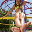 Little girl sitting at the playground on the beach — Stock Photo
