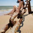 Young woman sitting at the beach — Stock Photo
