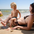 Mother playing with her kids on the beach — Stock Photo