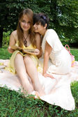 Two young girls sitting on coverlet upon green grass — Stock Photo