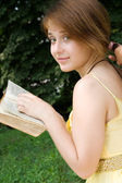 Young girl studying a book outdoors — Stock Photo