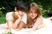 Two girls laying on the coverlet upon green grass — Stock Photo