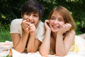 Girls pointing with finger on something smiling — Stock Photo